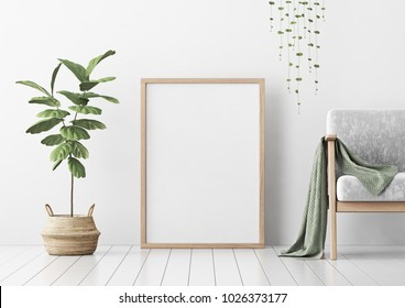 Interior poster mock up with vertical empty wooden frame standing on floor, gray armchair and tree in wicker basket in room with white wall. 3D rendering.