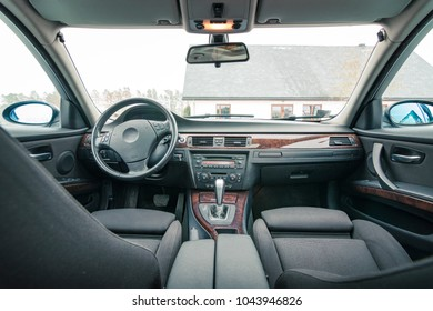 Interior of premium sedan car. Salon with seats, electronics, gauges, buttons, steering, mirrors and windows. Wooden panel and glass hatch.