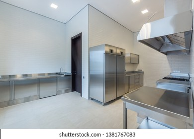 Interior of professional kitchen. Furniture, refrigerators, suspended cabinets, shelves, fully equipped tables, washstands