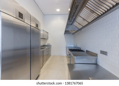 Interior of professional kitchen. Work tables, sinks, cupboards and refrigerator