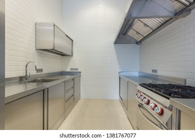 Interior of professional kitchen. Work tables, sinks, cupboards. One-piece work-top cooking range