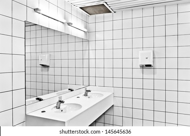 Interior of public restroom with taps, sinks, dryer and reflection in mirror
