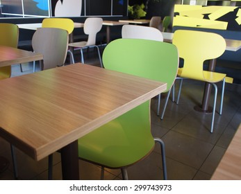 The interior of the restaurant fastfood with bright colored chairs and empty tables without visitors