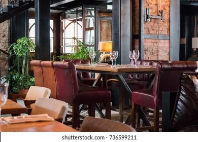 interior of restaurant in loft style sofas, brick walls, plants forged ladder