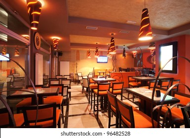 Interior of a restaurant, modern design in few colors, orange and brown.