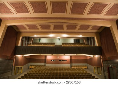 Interior of retro cinema auditorium with balcony in cubism style with line of chairs.