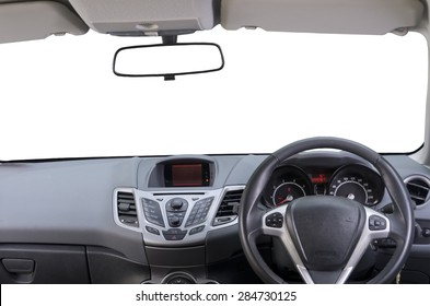 Interior of right hand drive car. Image shows driver controls, dashboard, central rear view mirror and sun visors. Windscreen (windshield) is isolated white, so as rear view mirror.