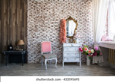 Interior room with a brick wall. The mirror in a gilded frame with curly boa. Pink lady's chair and table