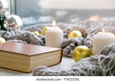 Interior of room with cozy window sill, Christmas decorations, books, candels, homely comfy rest concept. Hygge style. Still life.