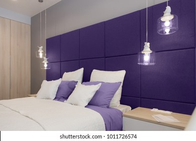 Interior of the room in light colors. Bedroom with bed and lighting in colors of the year 2018, ultra violet.