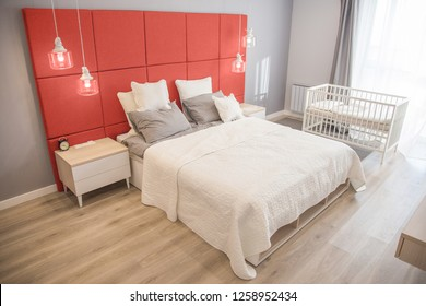 Interior of the room in light colors. Bedroom with a bed and a cot in colors of the year 2019 living coral