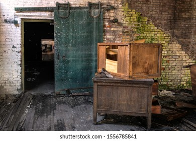 Interior of a room with and old desk, broken crate, moldy brick walls, and an interesting green door. Image taken at the old Scranton Lace Factory, built in 1890, closed in 2002, demolished in 2019.