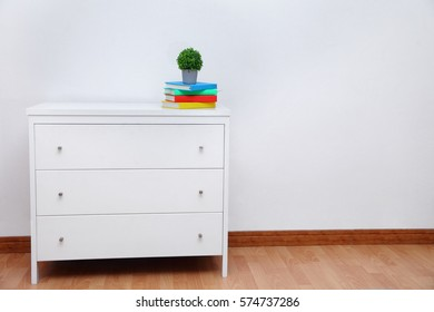 Interior of a room with wooden cabinet over white wall.Colorful book on console table in a classic living room interior.