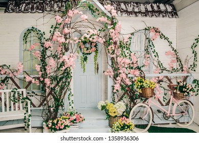 the interior of a rustic photo studio, the facade of a white building with a porch decorated with blooming flowers, baskets with flowers next to the steps and a pink bicycle