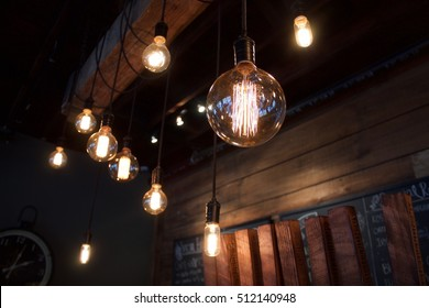 Interior shallow depth of field vintage electric light bulbs in the foreground with wooden slats in the background in dark dimly lit Western New York brew pub in East Aurora, New York, Erie County.