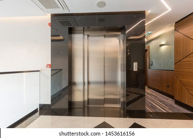 Interior of a shiny marble hotel corridor with elevator
