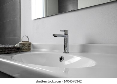 interior shot of a modern bathroom in the foreground the washbasin with a steel tap