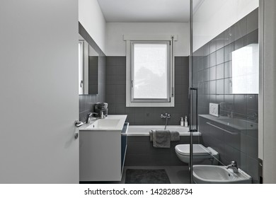 interior shot of a modern bathroom in the foreground the sink cabinet with built-in washbasin and steel tap