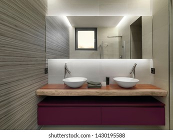 interior shot of a modern bathroom in the foreground the sink cabinets with two counter top washbasin on them