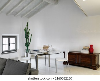 interior shot of a modern living room in the attic room in the foreground the glass dining table with white chairs and old trunk
