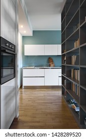interior shot of a modern white lacquered kitchen in the foreground the steel built-in ovens the floor is made of wood