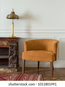 Interior shot of orange armchair and wooden vintage ornate sideboard and table lamp on off white wall and ornate carpet over wooden parquet floor
