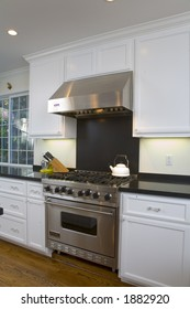 Interior shot of a recently remodeled kitchen featuring white custom cabinets, stainless steel appliances and an oak floor.