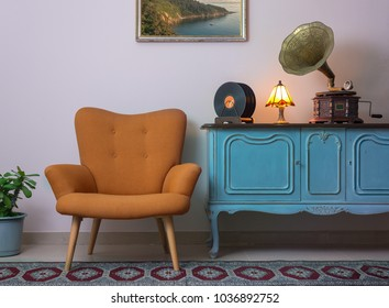 Interior shot of retro orange armchair, vintage wooden light blue sideboard, old phonograph (gramophone), vinyl records and illuminated table lamp on background of beige wall, and red carpet