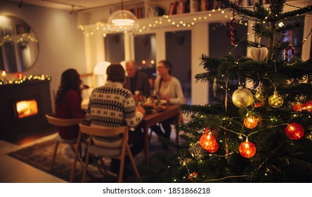 Interior shot of warm cozy Christmas decorated family home. Family sitting at dinner table having a Christmas eve dinner together.