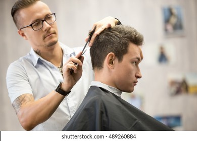Interior shot of working process in modern barbershop. Side view portrait of attractive young man getting trendy haircut. Male hairdresser serving client, making haircut using metal scissors and comb