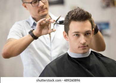 Interior shot of working process in modern barbershop. Close-up portrait of attractive young man getting trendy haircut. Male hairdresser serving client, making haircut using metal scissors and comb