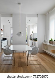 interior shots of a modern dining room with white table and white chairs, all overlooking the kitchen, the floor is made of wood