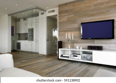 interior shots of a modern living room with wooden wainscoting , television and wooden floor overlooking on the kitchen