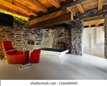 interior shots of a rustic living room with resin floor in the foreground the leather armchair and the rustic fireplace the walls are made of stone