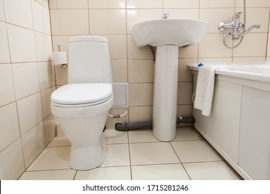 Interior of simple half bathroom with toilet, sink and bath with shower, a white sanitary ware