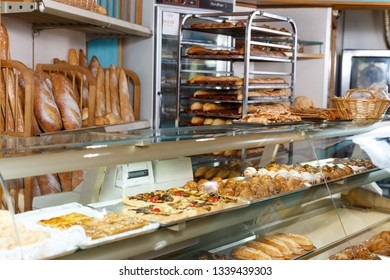 Interior of small bakery shop with racks and showcase full of pastries and baked goods