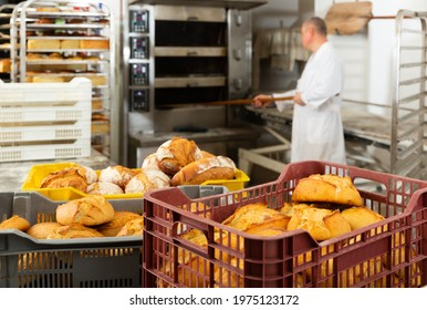 Interior of small bakeshop with box full of freshly baked bread. Breadmaking industry concept..