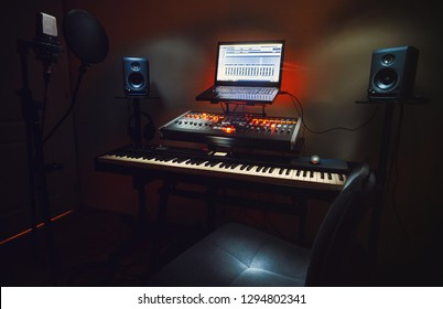 Interior of a small bedroom recording studio, details of equipment, microphone in foreground and modern mixing console with laptop in background.