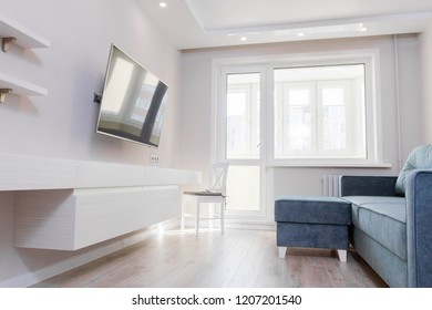 interior of a small bright room with a green sofa, TV. modern apartments
