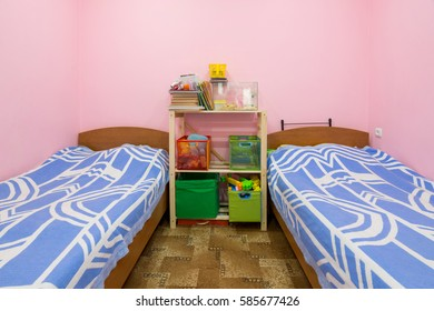 The interior of a small dorm room with two beds and a homemade rack in the middle