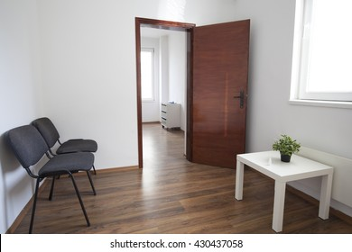 Interior of small empty doctor's consulting room and waiting room without people.
