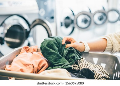interior of small laundromat in daylight. Close-up female holding basket. Girl loading dirty clothes inside drum and closing door. Self-service concept