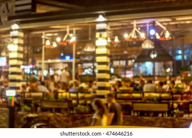 Interior of small restaurant blurred background. Blurred bokeh cafe interior in warm dark colors. Background for creative fashion design. Restaurant, coffee shop with beautiful background blur bokeh