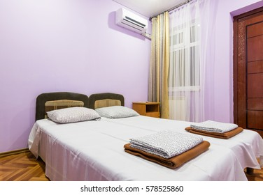 The interior of a small room with a double bed, a window