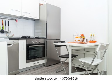Interior of Small White Kitchen with Fresh Fruit Basket on White Table With Two Chairs. Bright Modern Kitchen Interior Background. Must Have Kitchenware and Appliances, Stainless Fridge, Stove, Sink.