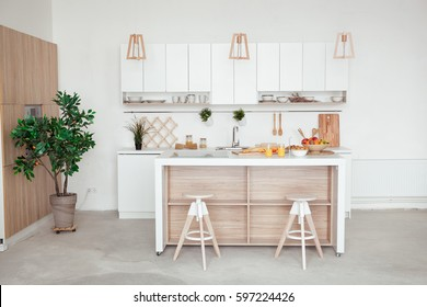 interior of small white kitchen with fresh fruit, two glasses of orange juice, baguette, red caviar, croissant and cookies with chocolate chips on the table