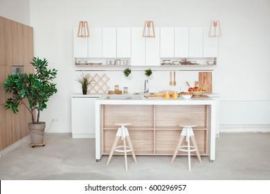 Inneneinrichtung einer kleinen weißen Küche mit frischem Obst, zwei Gläser Orangensaft, Baguette, rotem Kaviar, Croissant und Kekse mit Schokoladenchips auf dem Tisch