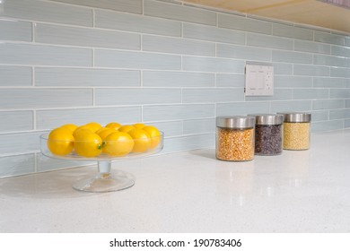 interior of small white kitchen with yellow lemons on the table
