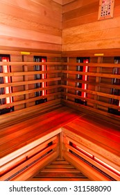 the interior of a small wooden infrarered sauna booth in a spa