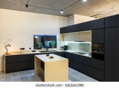interior of a spacious kitchen with black facades in the loft style.